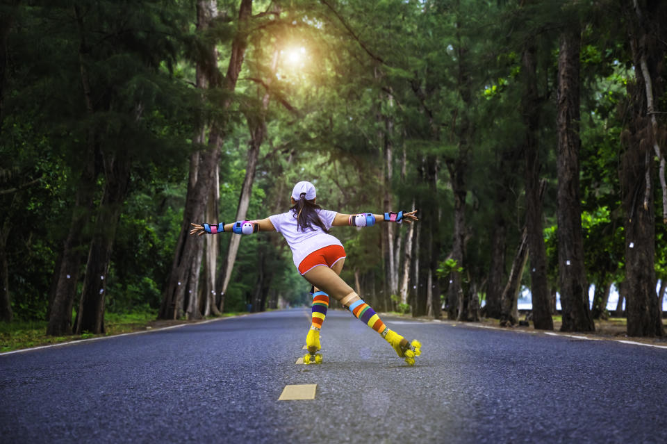Woman hipster in action of playful joyfully life of rolling skate on speed the roadster in middle of forest at morning light, cheerfully life freedom mind with enjoy the favorite sport personally