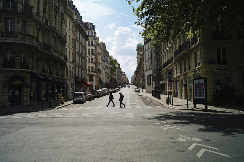 People cross a deserted street during nationwide confinement measures to counter the Covid-19, in Paris, Monday, April 27, 2020. France continues to be under an extended stay-at-home order until May 11 in an attempt to slow the spread of the COVID-19 pandemic. (AP Photo/Thibault Camus)