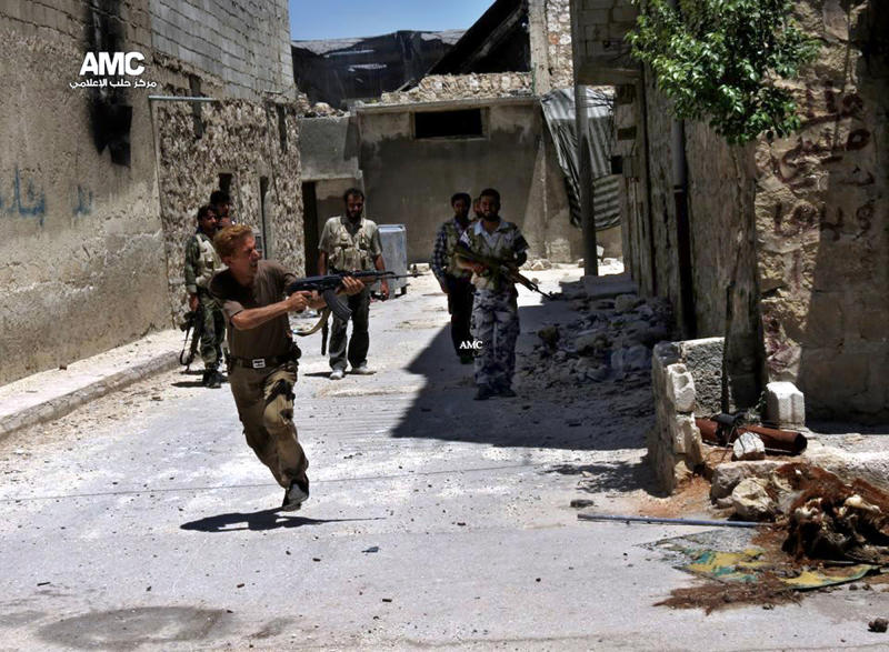 In this Tuesday, July 2, 2013 citizen journalism image provided by Aleppo Media Center AMC, which has been authenticated based on its contents and other AP reporting, a Syrian rebel fires his weapon during heavy clashes with Syrian soldiers loyal to Syrian President Bashar Assad near Aleppo International Airport in Aleppo, Syria. The British-based Syrian Observatory for Human Rights said fighting was fiercest in towns and villages in the strategic Aleppo. The province abuts the Turkish border, and is an important gateway for rebel fighters to bring in weapons and supplies. (AP Photo/Aleppo Media Center AMC)