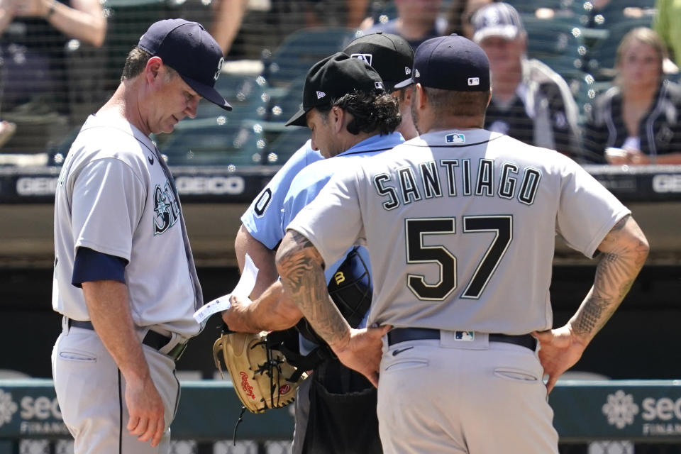 Seattle Mariners manager Scott Servais, left, listens to home plate umpire Phil Cuzzi about relief pitcher Hector Santiago, right, during the fifth inning in the first baseball game of a doubleheader against the Chicago White Sox in Chicago, Sunday, June 27, 2021. (AP Photo/Nam Y. Huh)