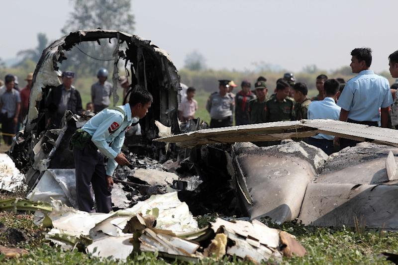 Myanmar army officials inspect the wreckage of a military passenger plane that crashed in a field near the airport in the capital of Naypyidaw on February 10, 2016 (AFP Photo/)
