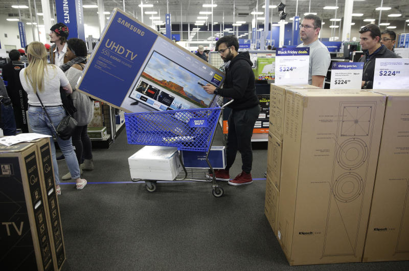 FILE- In this Nov. 22, 2018, file photo people wait in line to buy televisions as they shop during an early Black Friday sale at a Best Buy store on Thanksgiving Day in Overland Park, Kan. Best Buy Co., Inc. reports financial results Thursday, May 23, 2019. (AP Photo/Charlie Riedel, File)