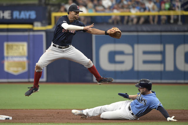 Boston Red Sox shortstop Xander Bogaerts flies over Tampa Bay Rays' Austin Meadows after forcing him out at second base and completing a double play at first base on Tommy Pham during the first inning of a baseball game Sunday, Sept. 22, 2019, in St. Petersburg, Fla. (AP Photo/Phelan M. Ebenhack)