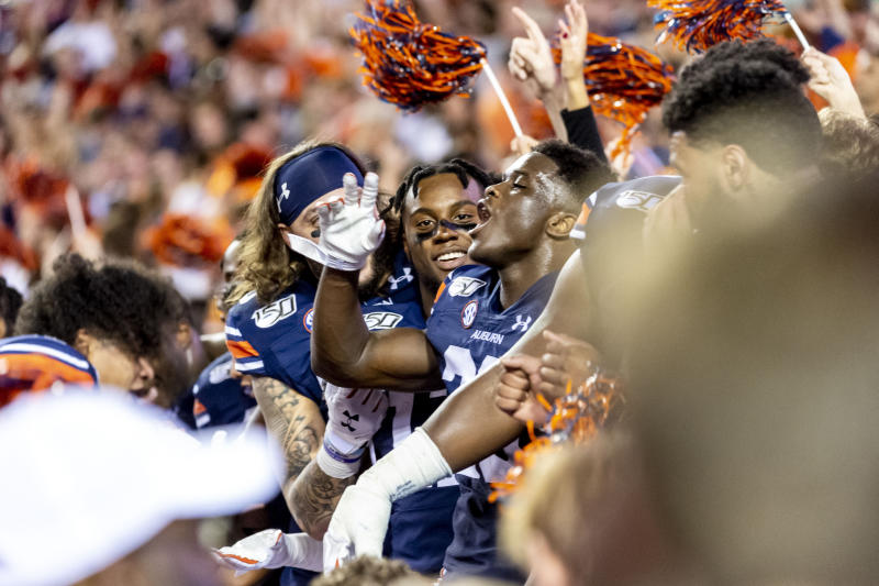 Auburn players sit in the student section as fans take the field to celebrate an upset of Alabama after an NCAA college football game, Saturday, Nov. 30, 2019, in Auburn, Ala. (AP Photo/Vasha Hunt)
