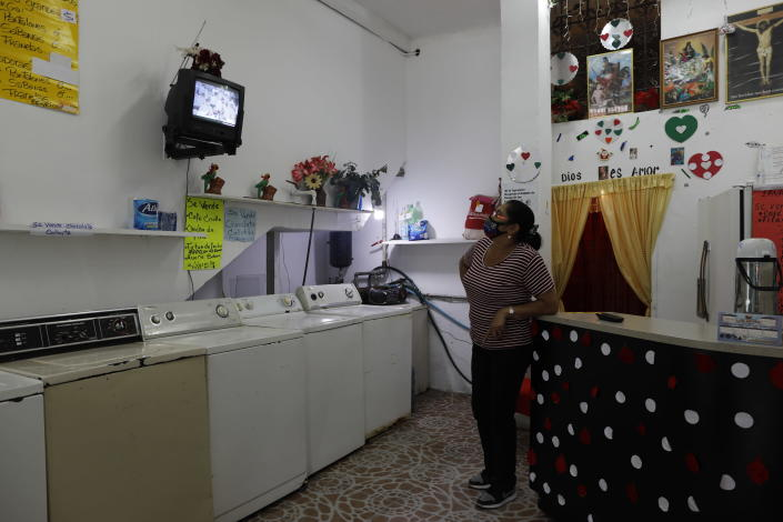 """Maria Comedor watches a live television broadcast of the Beatification ceremony for the late, Venezuelan Dr. Jose Gregorio Hernandez inside her washateria she operates in Caracas, Venezuela, Friday, April 30, 2021. Known as the """"doctor of the poor, Hernandez is being Beatified by the Catholic church, a step towards sainthood. (AP Photo/Ariana Cubillos)"""