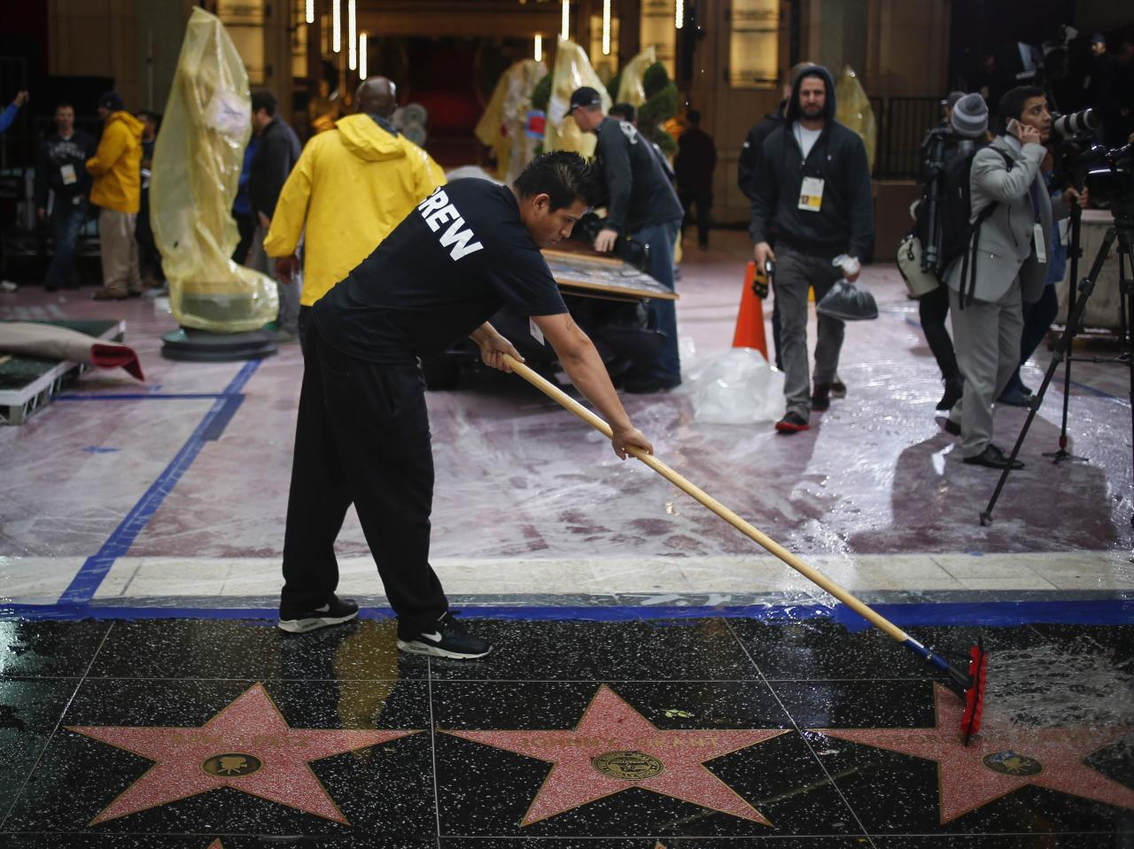 A man clears rain water from the entrance of the Dolby Theater ahead of the 86th Academy Awards in Hollywood, California March 1, 2014. The Oscars which will be presented at the Dolby Theater on March 2, 2014. REUTERS/Adrees Latif (UNITED STATES - Tags: ENTERTAINMENT)