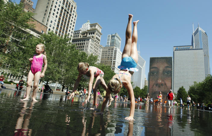 From left, Amelia Schendel, her sister Alison Schendel and Madeline Ahern, all on vacation from Minnesota, enjoy the cool water on a hot summer day at Crown Fountain in Chicago's Millennium Park, Wednesday, June 27, 2012. Temperatures in Illinois are forecast to top 100 degrees by Thursday, and authorities are urging the public to be cautious. (AP Photo/Sitthixay Ditthavong)