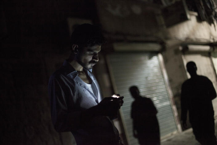 In this Friday, Sept. 21, 2012 photo, a Syrian man looks at his mobile phone in the Bustan al-Qasr neighborhood of Aleppo, Syria. The Britain-based Syrian Observatory for Human Rights said Friday that nearly 30,000 Syrians have been killed during the 18-month uprising against the Assad regime. (AP Photo/ Manu Brabo)