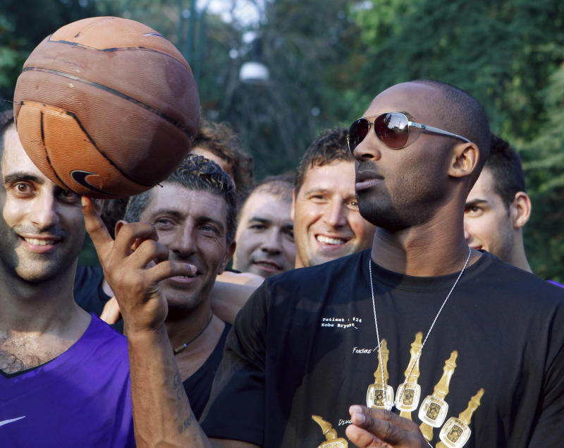 "U.S. basketball star Kobe Bryant plays with a ball during a sponsor's appearance in Milan, Italy, Wednesday, Sept. 28, 2011. Bryant said it's ""very possible"" he will play in Italy during the NBA lockout, adding the country is like home because he spent part of his childhood there.  (AP Photo/Luca Bruno)"