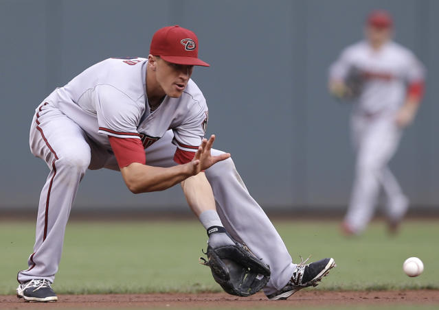 Arizona Diamondbacks shortstop Nick Ahmed fields a ground ball hit by Cincinnati Reds' Todd Frazier in the first inning of a baseball game, Monday, July 28, 2014, in Cincinnati. Ahmed threw Frazier out at first. (AP Photo/Al Behrman)