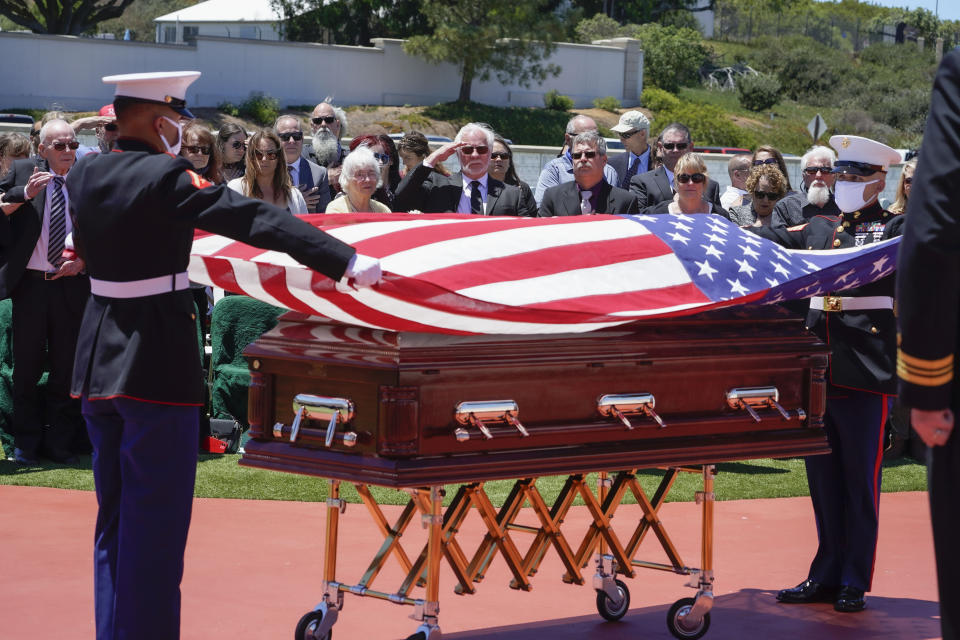 A military honor guard drapes a U.S. flag over the casket of Marine Corps, Pfc. John Franklin Middleswart for a full military honors at Fort Rosecrans National Cemetery, Tuesday, June 8, 2021 in San Diego. Eighty years after he died in the attack on Pearl Harbor and just months after his remains were finally identified, the California Marine has been laid to rest with full military honors. About 50 people attended the ceremony Tuesday for Middleswart in his hometown of San Diego, the Union-Tribune reported. (Nelvin C. Cepeda/The San Diego Union-Tribune via AP)