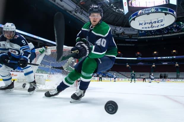 Vancouver Canucks' Elias Pettersson reaches for the puck in a game against Winnipeg.