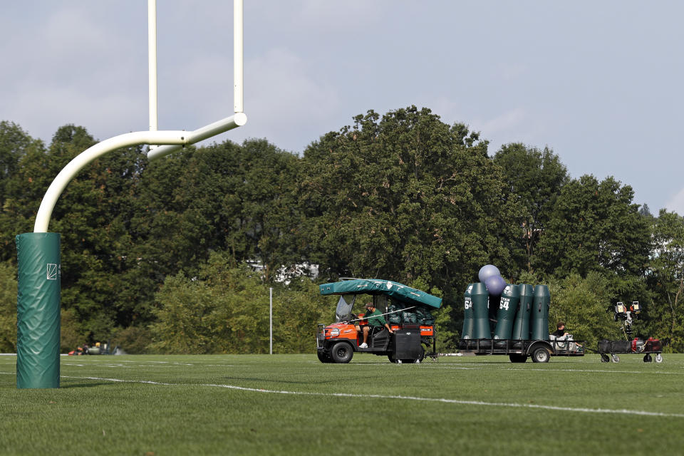 Empty Jets practice field with uprights, cart carrying equipment.