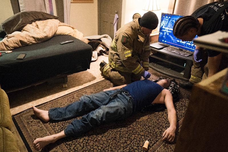 Manchester, New Hampshire firefighters assess the condition of a 35-year-old man who had overdosed on heroin in 2018. The man was revived with two doses of Narcan (AFP Photo/Don EMMERT)