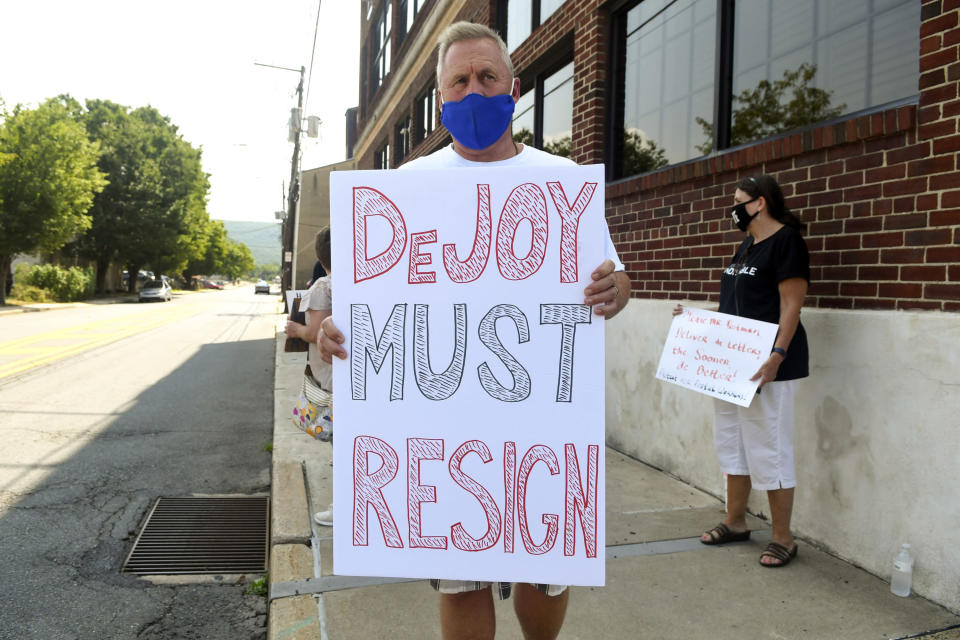 "Todd Zimmerman, of Mantzville, Pa., holds a sign ""DeJoy Must Resign"" during a peaceful protest with the Schuylkill Democratic Action Group in front of the office of U.S. Rep. Dan Meuser, R-9, on Progress Avenue in Pottsville, Pa., on Thursday, Aug. 27, 2020. (Jacqueline Dormer/Republican-Herald via AP)"