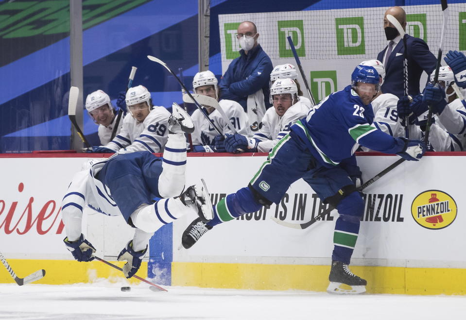 Vancouver Canucks' Alexander Edler, right, of Sweden, and Toronto Maple Leafs' Zach Hyman collide during the second period of an NHL hockey game in Vancouver, British Columbia, Sunday, April 18, 2021. Edler received a major penalty for kneeing and game misconduct on the play. (Darryl Dyck/The Canadian Press via AP)