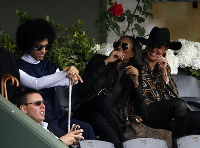 U.S pop singer Prince, top left and unidentified women, watch Spain's Rafael Nadal playing Serbia's Dusan Lajovic during their fourth round match of the French Open tennis tournament at the Roland Garros stadium, in Paris, France, Monday, June 2, 2014. (AP Photo/Darko Vojinovic)