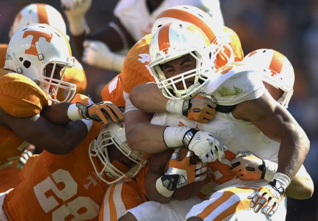 Tennessee running back Justus Pickett (31) is tackled by Tennessee defense while carrying the ball during the second half of the Orange and White game at Neyland Stadium in Knoxville, Tenn., Saturday, April 12, 2014. (AP Photo/Knoxville News Sentinel, Amy Smotherman Burgess)
