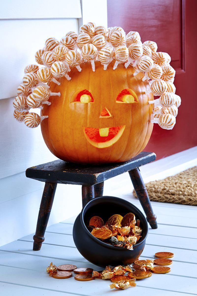 """<p>Hollow out a medium pumpkin from the bottom. Carve a half-circle mouth with a tooth, two half-circle eyes with pupils, and triangle nose. </p><p>For eyes, push in inner piece (don't remove!). Then, etch away skin on pupils and tooth with linoleum cutter. Use an awl to poke holes about 1 1/2"""" apart across top and sides of pumpkin. Push <span class=""""redactor-unlink"""">lollipops</span> into holes to create hair.</p>"""