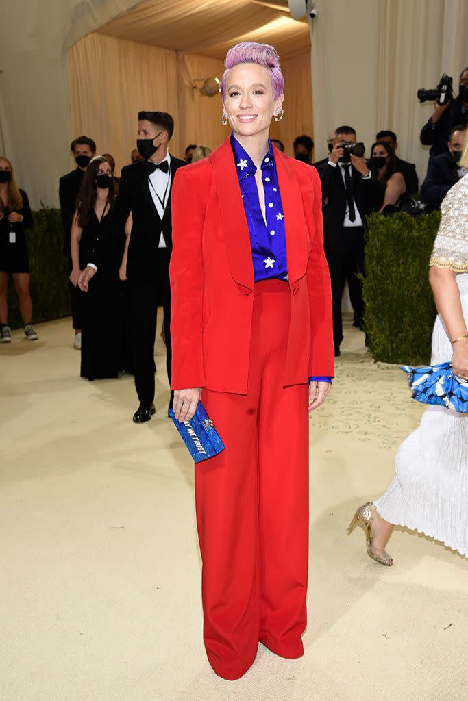 Megan Rapinoe in a Sergio Hudson suit, Giuseppe Zanotti platform boots and an Edie Parker clutch. - Credit: AP Images