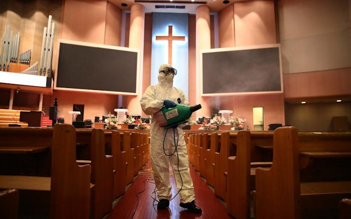 A disinfection worker wearing protective clothing sprays anti-septic solution in an Yoido Full Gospel Church - Getty