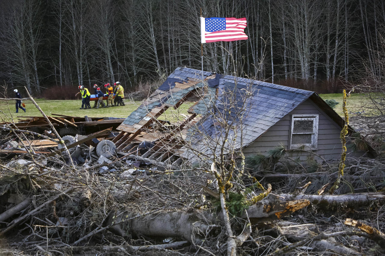 Rescue workers remove a body from the wreckage of homes destroyed by a mudslide near Oso, Wash, Monday, March 24, 2014. The search for survivors of Saturday's deadly mudslide grew Monday to include scores of people who were still unaccounted for as the death toll from the wall of trees, rocks and debris that swept through the rural community rose to at least 14. (AP Photo/seattlepi.com, Joshua Trujillo)