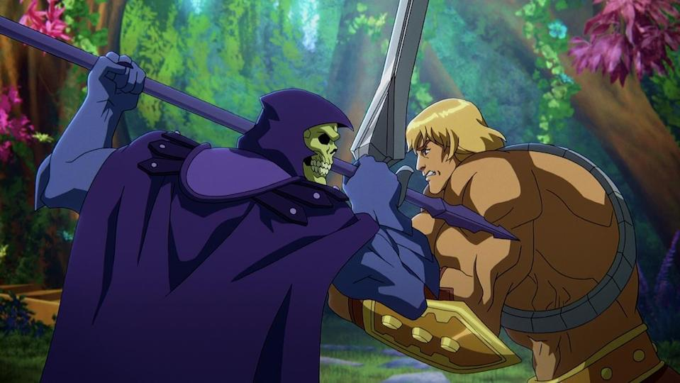 Skeletor and He-Man stand face to face with weapons in a forest