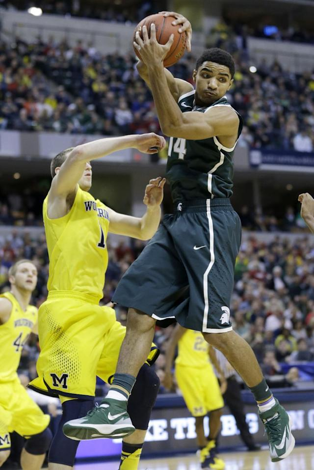 Michigan State guard Gary Harris (14) grabs a rebound over Michigan guard Nik Stauskas (11) in the first half of an NCAA college basketball game in the championship of the Big Ten Conference tournament Sunday, March 16, 2014, in Indianapolis. (AP Photo/Michael Conroy)