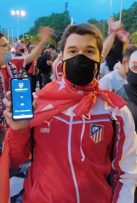 Fan of Spain's Atletico Madrid poses for a picture as he holds a phone with Chiliz's Socios.com app, in Madrid