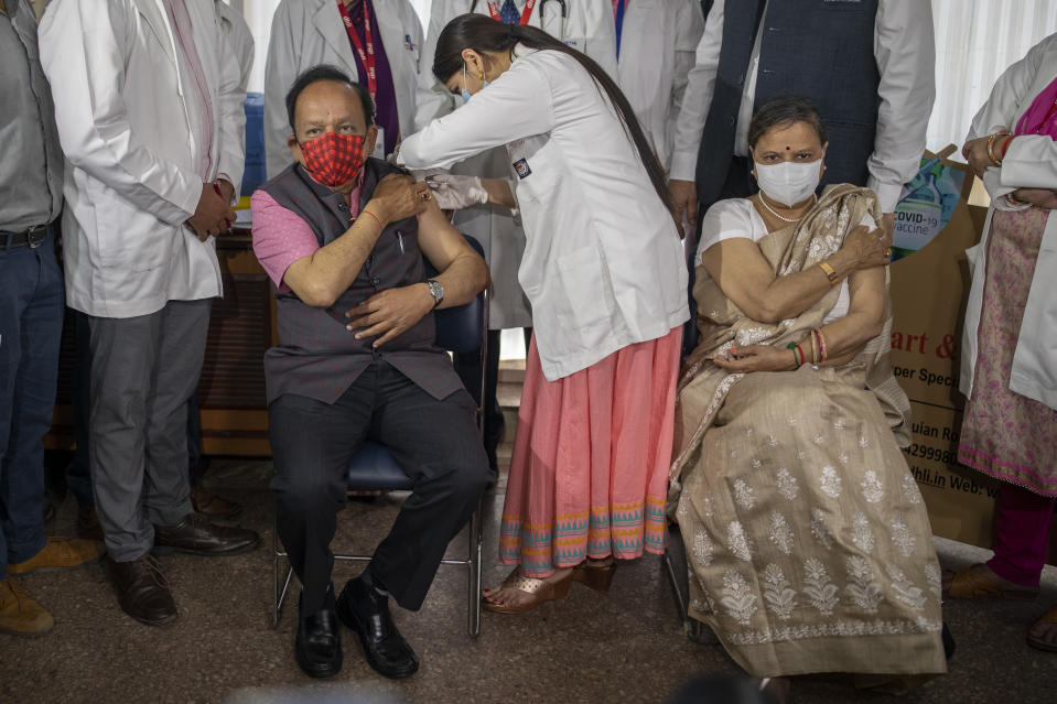 Indian Health Minister Harsh Vardhan is administered the COVAXIN vaccine, developed by Indian company Bharat Biotech, with his wife Nutan Goel sitting next to him after receiving her shot at a private hospital in New Delhi, India, Tuesday, March 2, 2021. India is expanding its coronavirus vaccination drive beyond health care and front-line workers, offering the shots to older people and those with medical conditions that put them at risk. (AP Photo/Altaf Qadri)