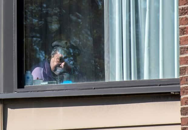 A resident gazes out his window in the morning sun at Hawthorn Place Care Centre in Toronto on May 10, 2021. (Frank Gunn/The Canadian Press - image credit)