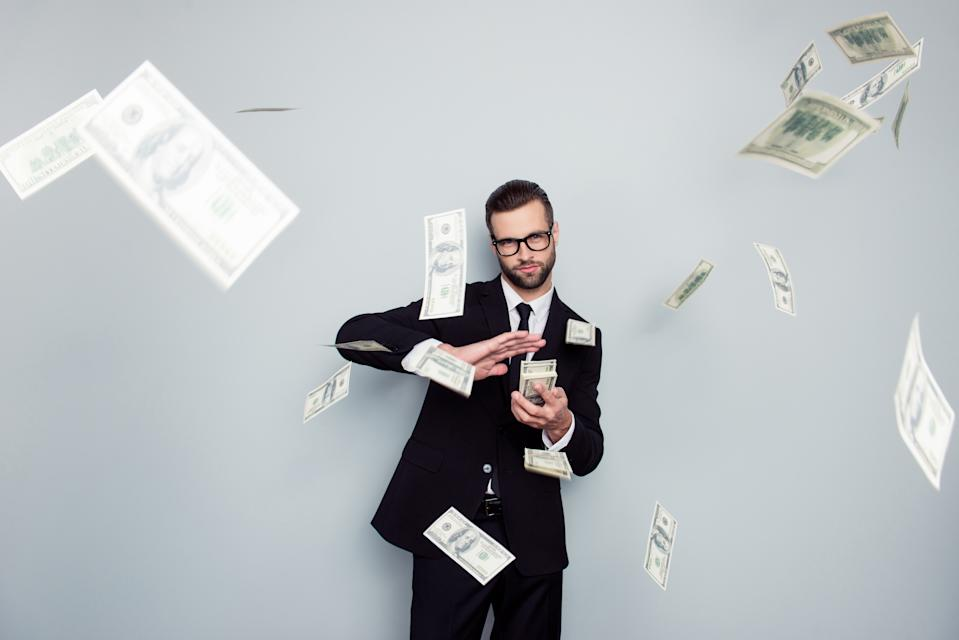 Entrepreneur wearing a suit and glasses throwing a stack of money in front of a grey background.