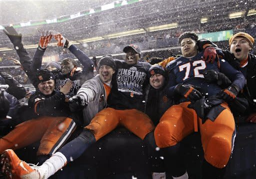 Syracuse players, including guard Ivan Foy (72), celebrate with fans after the team defeated West Virginia 38-14 in the Pinstripe Bowl NCAA college football game at Yankee Stadium in New York, Saturday, Dec. 29, 2012. (AP Photo/Kathy Willens)