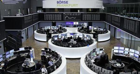 Traders work at their desks in front of the German share price index, DAX board, at the stock exchange in Frankfurt, Germany, November 30, 2016.      REUTERS/Staff/Remote