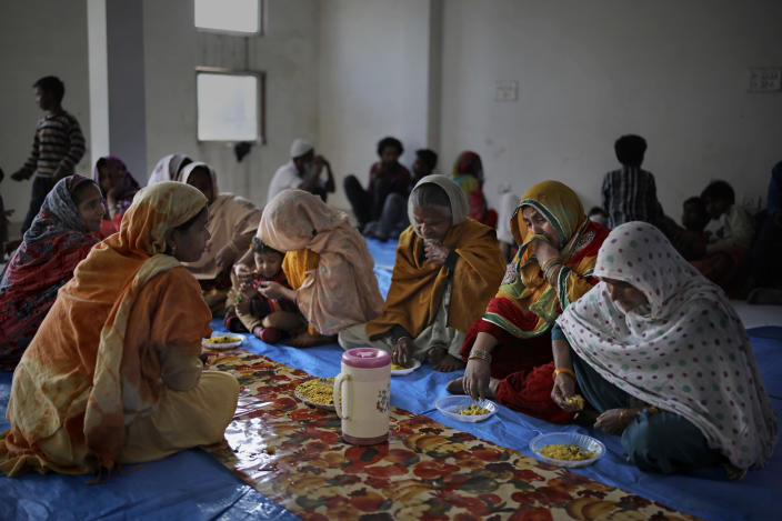In this Friday, Feb. 28, 2020 photo, Muslim women, who were rescued after their homes were attacked by a marauding Hindu mob, sob while eating a meal inside a hall which doubles as a shelter at Al-Hind hospital in Old Mustafabad neighborhood of New Delhi, India. The hospital in the riot-torn neighborhood turned from a community clinic into a trauma ward, its doctors, for the first time, dealing with injuries like gunshot wounds, crushed skulls and torn male genitals. Authorities haven't said what sparked the violence that has left more than 40 dead and hundreds injured, but it was the culmination of growing tensions since the passage of a citizenship law in December that fast-tracks naturalization for some religious minorities from neighboring countries but not Muslims. (AP Photo/Altaf Qadri)