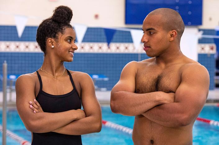 Swimmers Jayla and Troy Pina smile at each other with their arms crossed, a swimming pool in the background