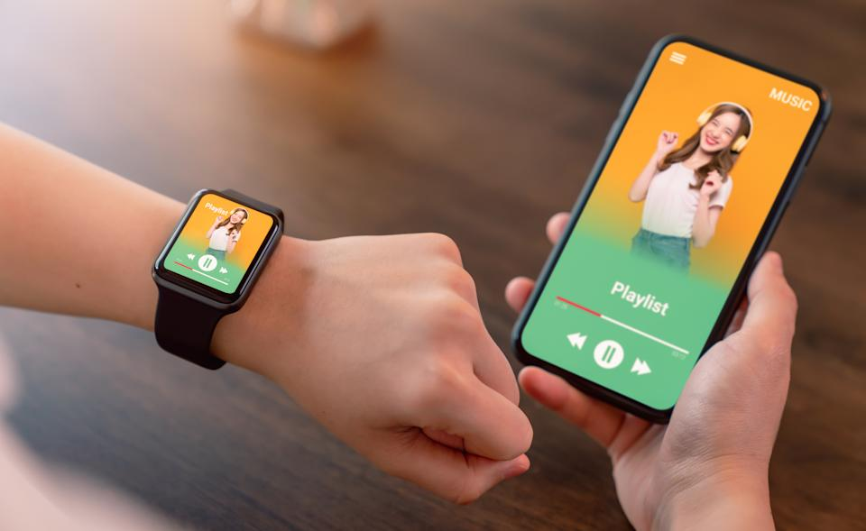 Hand wearable smartwatch and holding smartphone with show application music favourite playlist screen.