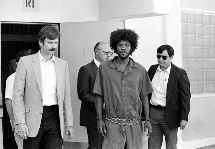 FILE - In this July 31, 1983, file photo, Kevin Cooper, center, a suspect in connection with the slashing death of four people in Chino, Calif., is escorted to a car for transport to San Bernadino from Santa Barbara, Calif., after he was arrested by police at Santa Cruz Island. Gov. Gavin Newsom has ordered an independent investigation into the conviction of death row inmate Kevin Cooper, who claims he was framed for the stabbing deaths of four people, including two children, in 1983. Newsom on Friday, May 28, 2021, ordered a law firm to examine all the evidence, including results of DNA testing that Cooper had argued could prove his innocence. Newsom said he's taking no position on Cooper's guilt or innocence. Cooper wants clemency, alleging he was framed for a 1983 knife and hatchet attack on a Chino Hills family that killed four people, including a boy and girl, ages 10 and 11. (AP Photo/File)