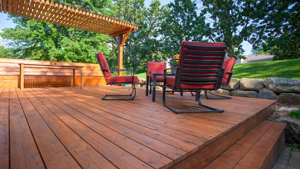 Backyard deck with deck chairs and a pergola on a sunny summer day.