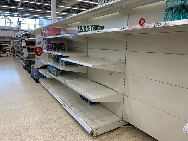 Empty shelves in the water aisle of the Tesco store at St Rollox in Glasgow (Andrew Milligan/PA)