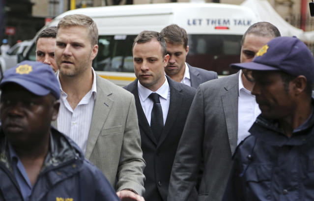 Oscar Pistorius, center rear, arrives at the high court for the third day of his trial in Pretoria, South Africa, Wednesday, March 5, 2014. Pistorius is charged with murder with premeditation in the shooting death of girlfriend Reeva Steenkamp in the pre-dawn hours of Valentine's Day 2013. (AP Photo/Schalk van Zuydam)
