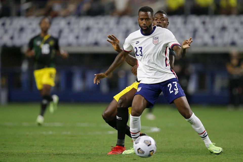 United States midfielder Kellyn Acosta attempts to gain control of the ball in front of Jamaica forward Cory Burke.