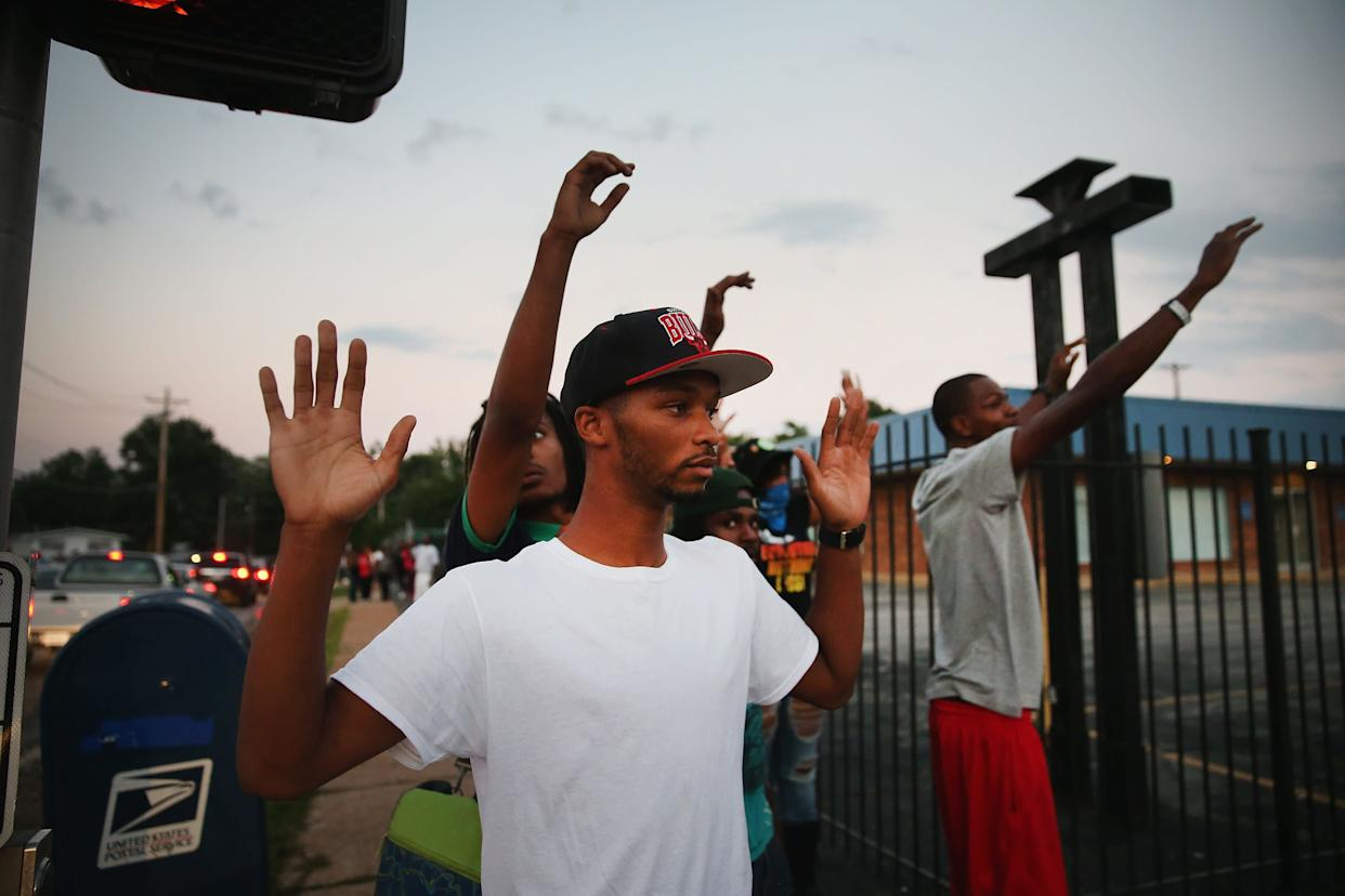 FERGUSON, MO - AUGUST 11: Protesters are forced by police from the business district into nearby neighborhoods on August 11, 2014 in Ferguson, Missouri. Police responded with tear gas and rubber bullets as residents and their supporters protested the shooting by police of an unarmed black teenager named Michael Brown who was killed Saturday in this suburban St. Louis community. Yesterday 32 arrests were made after protests turned into rioting and looting in Ferguson. (Photo by Scott Olson/Getty Images)