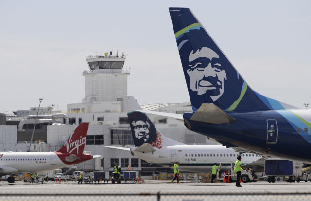 A Virgin America and Alaska Airlines plane sit parked in a terminal. Alaska recently bought Virgin for $2.6 billion in 2016. (AP Photo/Ted S. Warren)
