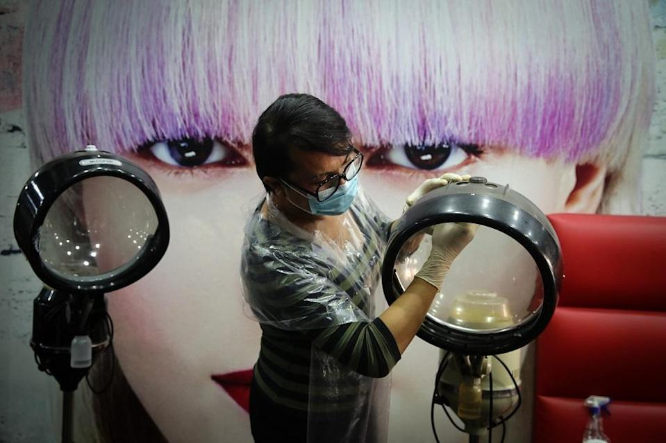 A worker disinfects equipment at a hair salon in Shah Alam June 8, 2020. — Picture by Yusof Mat Isa