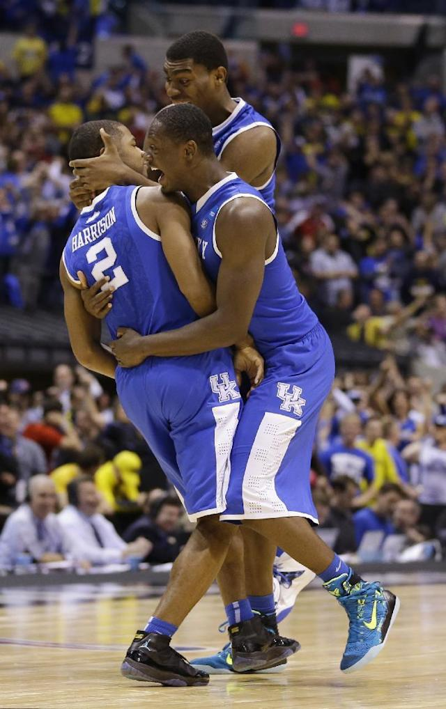 Kentucky's Aaron Harrison (2) is congratulated by teammates Julius Randle and Dakari Johnson after making a three-point basket in the final seconds of the second half of an NCAA Midwest Regional final college basketball tournament game against Michigan Sunday, March 30, 2014, in Indianapolis. Kentucky won 75-72 to advance to the Final Four. (AP Photo/Michael Conroy)