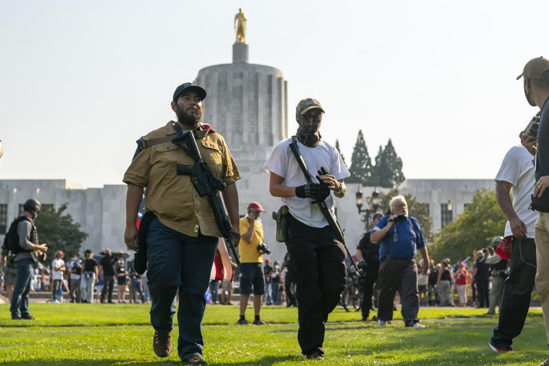 Far-right protesters walk past the state capitol with long rifles during a rally on September 7, 2020 in Salem, Oregon. A Pro-Trump caravan drove into the Oregon state capitol Monday afternoon where far-right protesters clashed with counter protesters. (Nathan Howard/Getty Images)