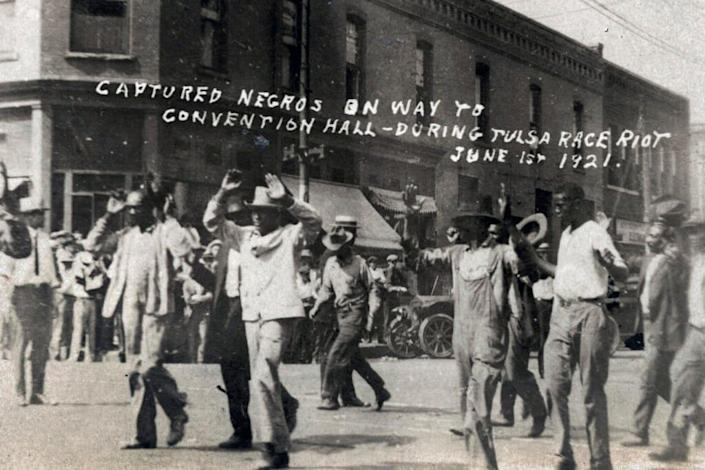 In this photo provided by the Department of Special Collections, McFarlin Library, The University of Tulsa, a group of Black men are marched past the corner of 2nd and Main Streets in Tulsa, Okla., under armed guard during the Tulsa Race Massacre on June 1, 1921. (Department of Special Collections, McFarlin Library, The University of Tulsa via AP, File)