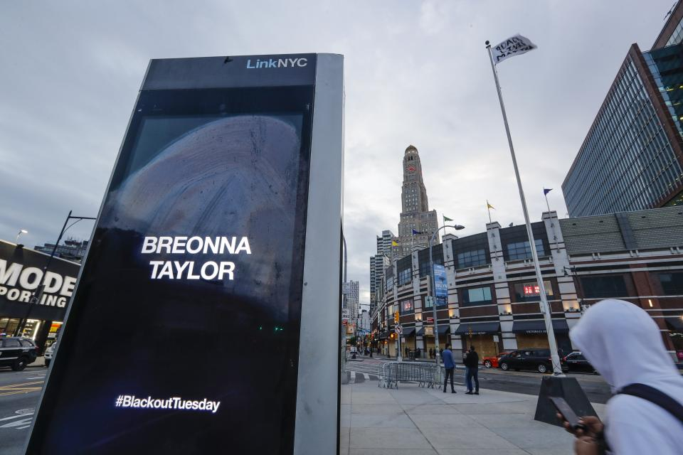A pedestrian passes a Link NYC kiosk showing Breonna Taylor's name after protesters gathered to rally for George Floyd, Tuesday, June 2, 2020, in the Brooklyn borough of New York. (AP Photo/Frank Franklin II)