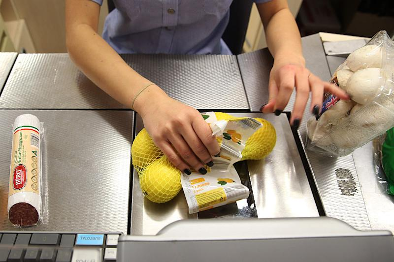 An employee scans a bag of lemons at the check-out counter of an Aldi Stores Ltd. food store in Sydney, Australia, on Thursday, June 25, 2015.